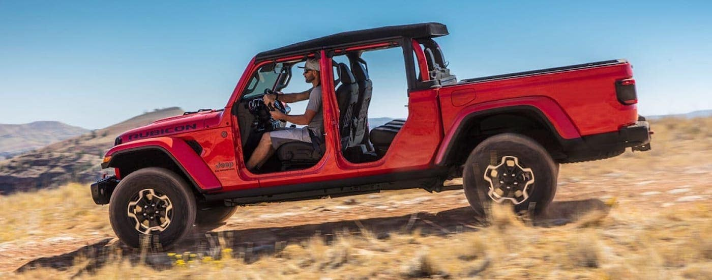 A red Gladiator with no doors is shown from the side driving in a field after winning the 2020 Jeep Gladiator vs 2020 Chevy Colorado comparison.