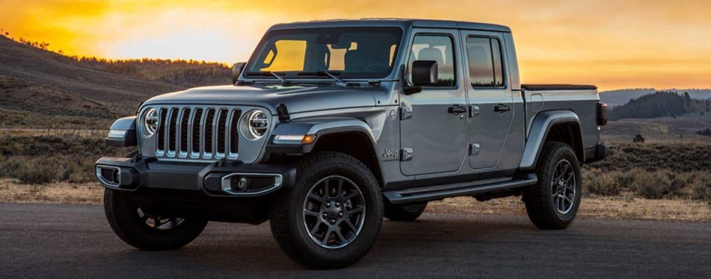 A silver 2020 Jeep Gladiator is parked on a gravel road outside Costa Mesa at sunset.