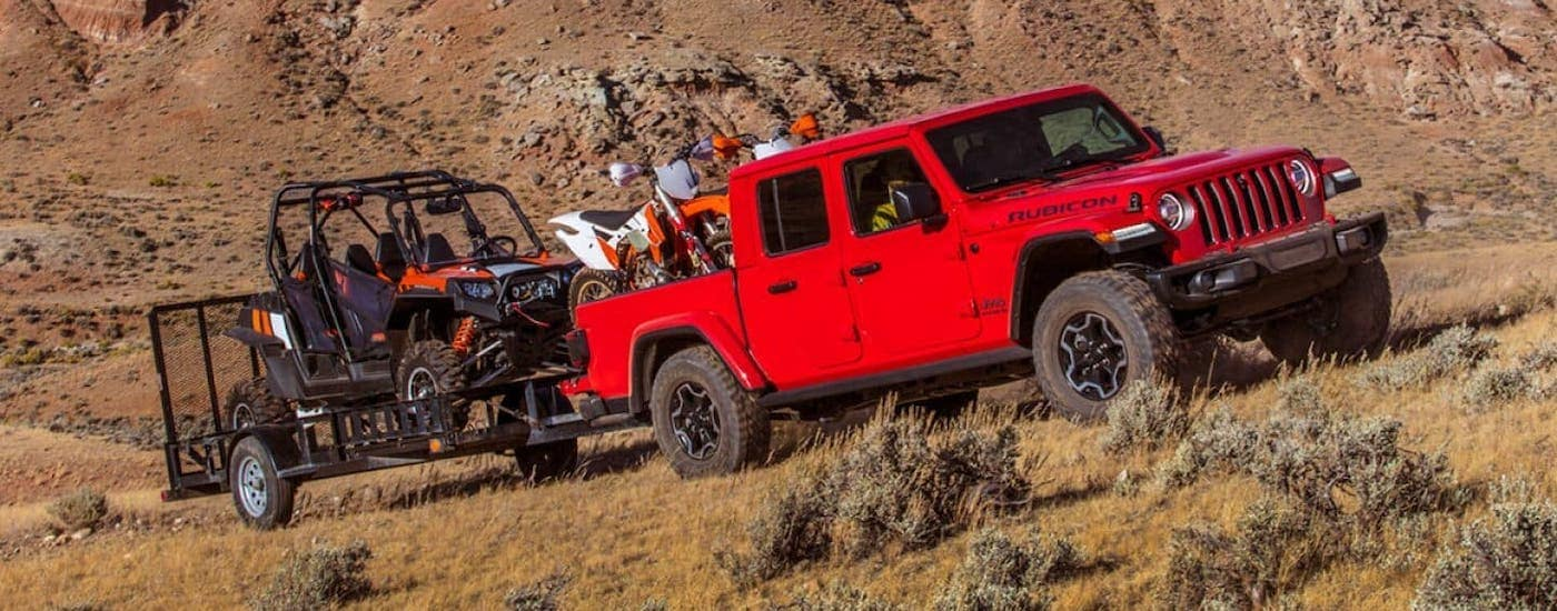 A red 2020 Jeep Gladiator is towing a side-by-side and dirt bikes in a desert outside Costa Mesa.