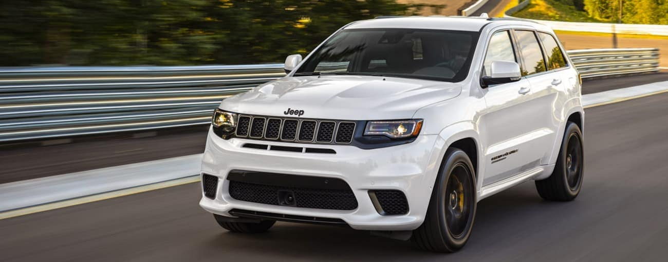 A white 2020 Jeep Grand Cherokee Trackhawk is racing on a track.