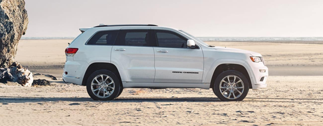 A white 2020 2020 Jeep Grand Cherokee is shown from the side parked on the beach.