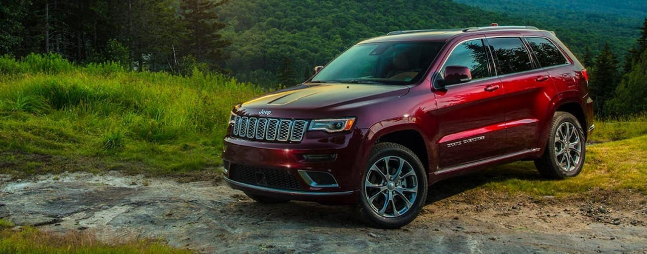 A red 2020 Jeep Grand Cherokee is parked off-road near the woods after winning the 2020 Jeep Grand Cherokee vs 2020 Honda Passport comparison.
