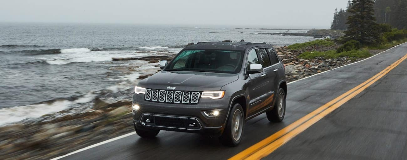 A grey 2020 Jeep Grand Cherokee is driving past the ocean in the rain near Costa Mesa, CA.