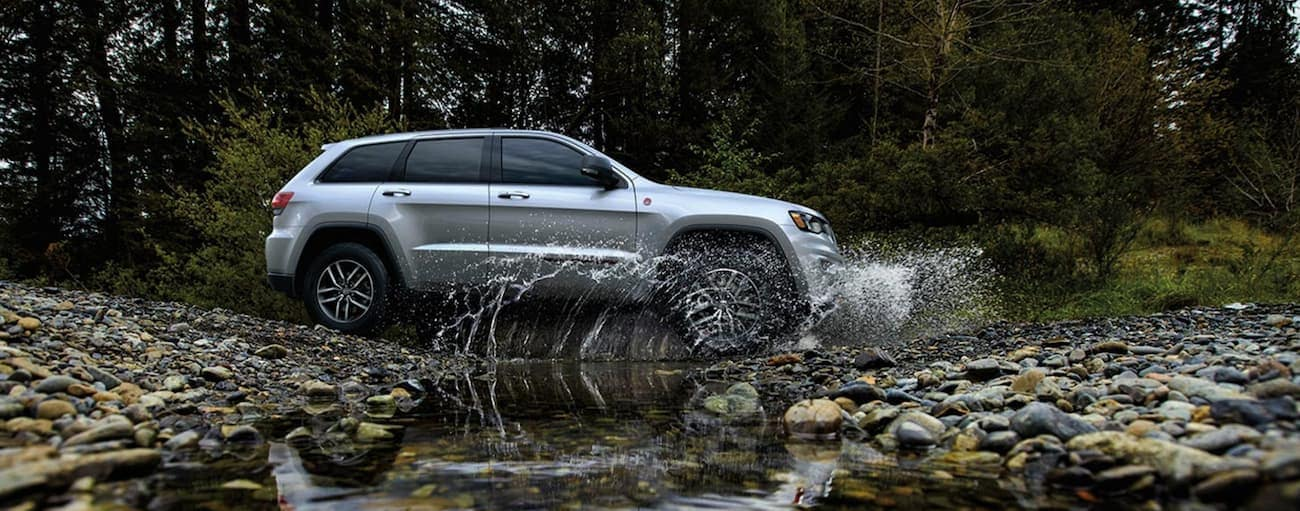 A silver 2020 Jeep Grand Cherokee is crossing a river while off-roading after winning the 2020 Jeep Grand Cherokee vs 2020 Toyota 4Runner comparison.