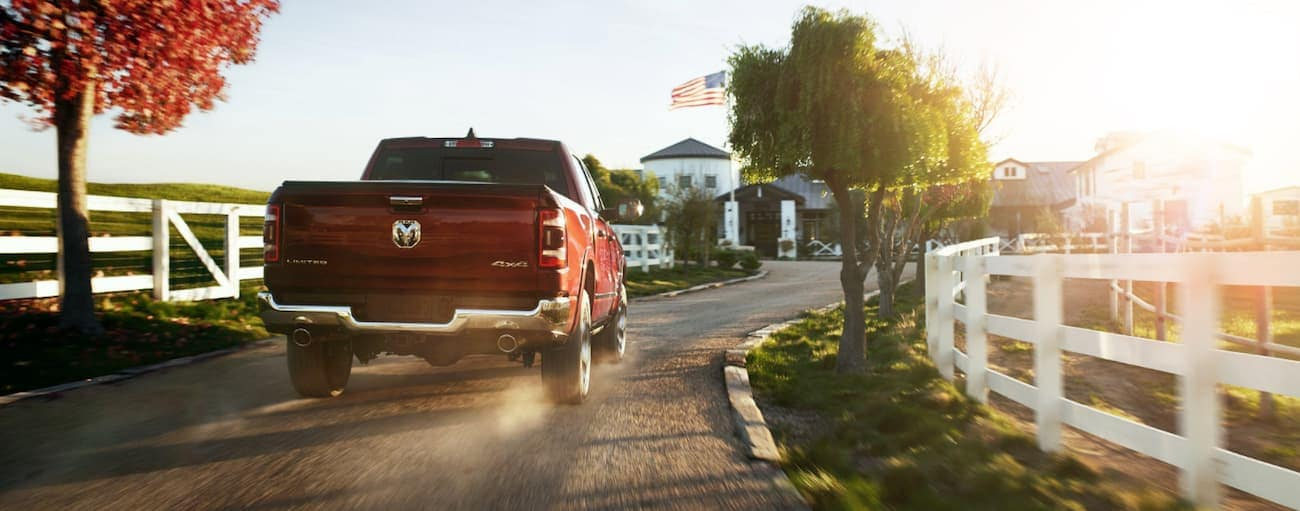 A red 2020 Ram 1500 is driving down a dirt driveway toward a farm after winning the 2020 Ram 1500 vs 2020 GMC Sierra 1500 comparison.