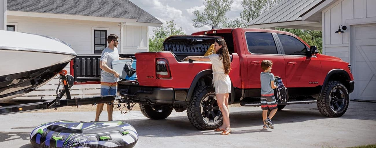 A family is loading up beach gear into the bed of a red 2020 Ram 1500.