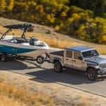 A silver 2020 Jeep Gladiator is towing a boat on a highway, shown from a high angle.