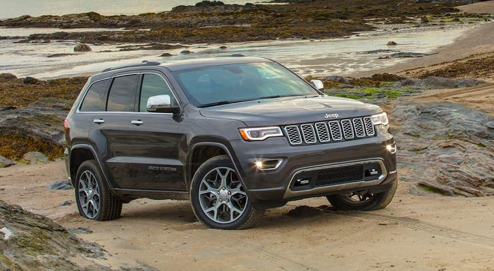 A grey 2020 Jeep Grand Cherokee is parked on the beach near Costa Mesa, CA.