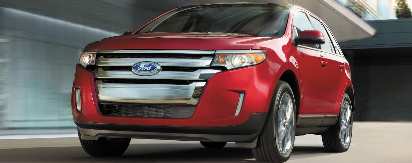 A red 2014 Ford Edge is driving on a city street.