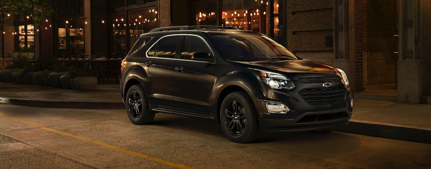 A black 2017 Chevy Equinox is on a city street at night.
