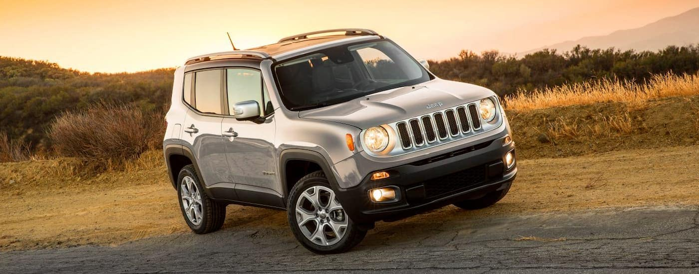 A silver 2018 Jeep Renegade is parked on a road side at sunset.