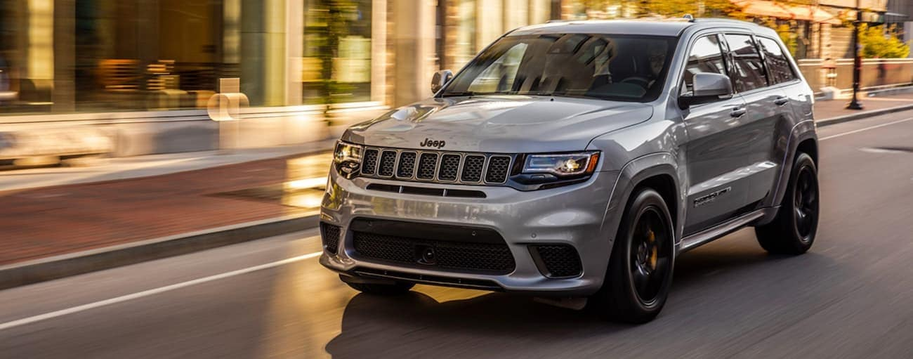 A grey 2020 Jeep Grand Cherokee is driving on a wet city street after winning the 2020 Jeep Grand Cherokee vs 2020 Ford Explorer comparison.