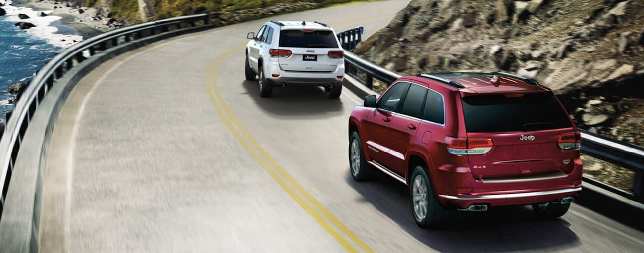 A red 2020 Jeep Grand Cherokee is following a white one on a winding road next to the ocean near Costa Mesa, CA.