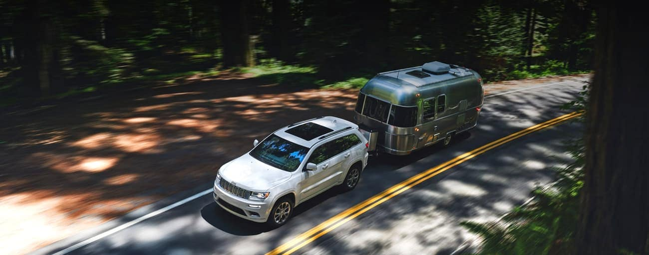 A white 2020 Jeep Grand Cherokee is shown from above towing an Airstream on a road through the woods.