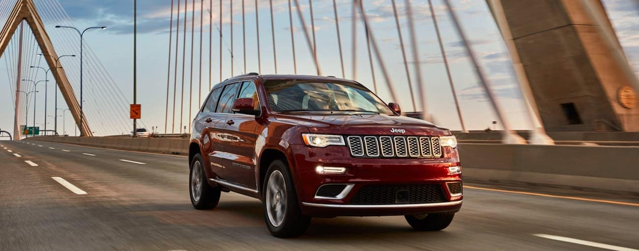 A red 2020 Jeep Grand Cherokee is driving over a bridge after winning the 2020 Jeep Grand Cherokee vs 2020 Toyota Highlander comparison.