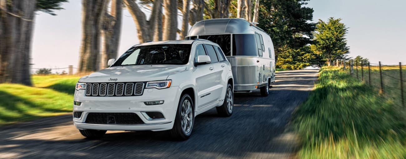 A white 2020 Jeep Grand Cherokee is towing an Airstream trailer on a tree-lined road near Costa Mesa, CA.