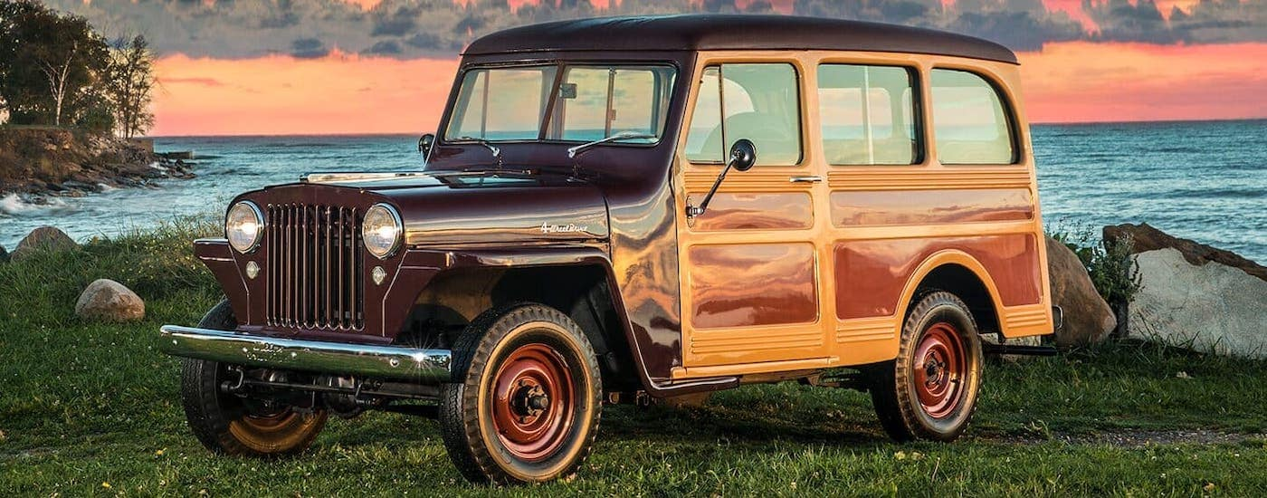 A burgundy wood-paneled Jeep model, a 1940s Willys Station Wagon, is parked in front of the ocean and a vibrant sunset.