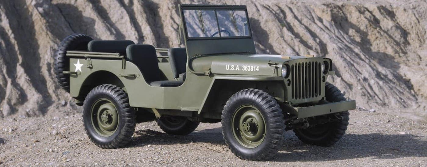 A military-green 1943 Jeep Willys MB is parked in a gravel quarry.