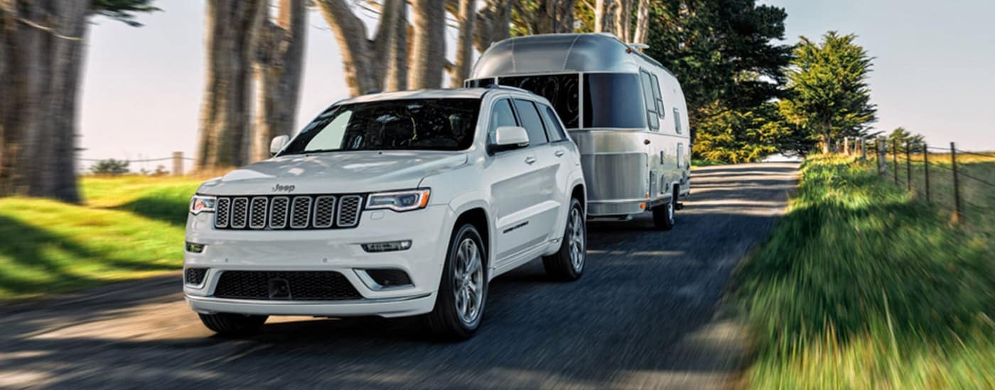 A white 2020 Jeep Grand Cherokee is towing an Airstream on a tree-lined road.