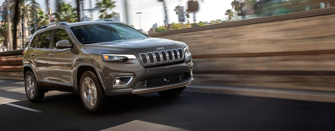 A grey 2020 Jeep Cherokee is driving on a highway with palm trees.
