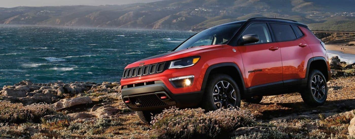 A red 2020 Jeep Compass is parked on a rocky beach after winning the 2020 Jeep Compass vs 2020 Toyota RAV4 comparison.