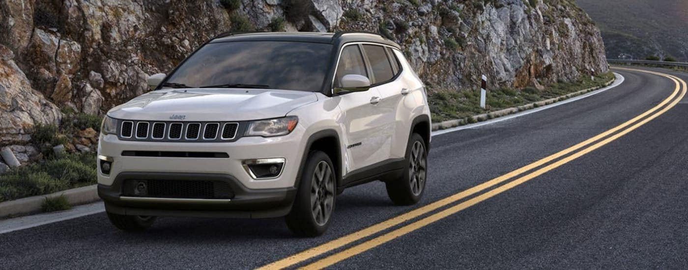 A white 2020 Jeep Compass is driving around a rocky highway near Costa Mesa, CA.