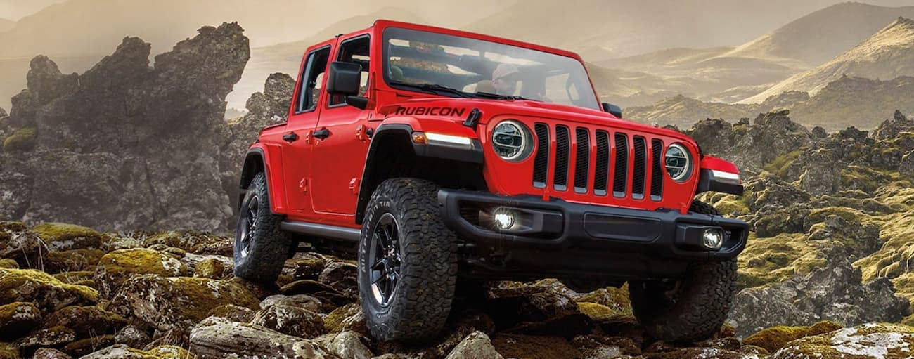 A red 2020 Jeep Wrangler Unlimited is off-roading on rocky mountain terrain.
