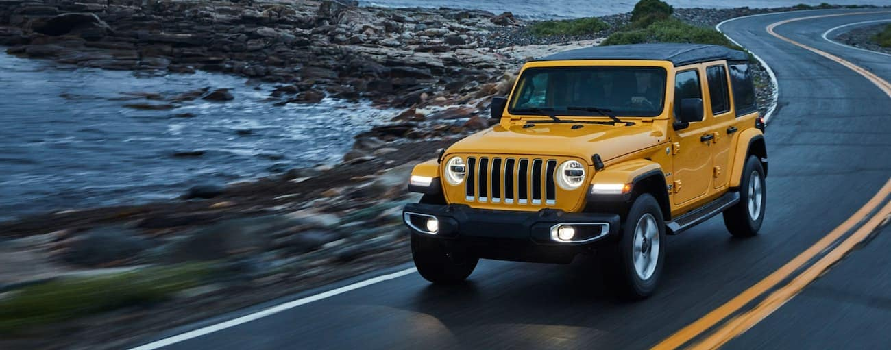 A yellow 2020 Jeep Wrangler Unlimited is driving in the rain past a rocky ocean shore near Costa Mesa, CA, after winning the 2020 Jeep Wrangler Unlimited vs 2020 Toyota 4Runner comparison.