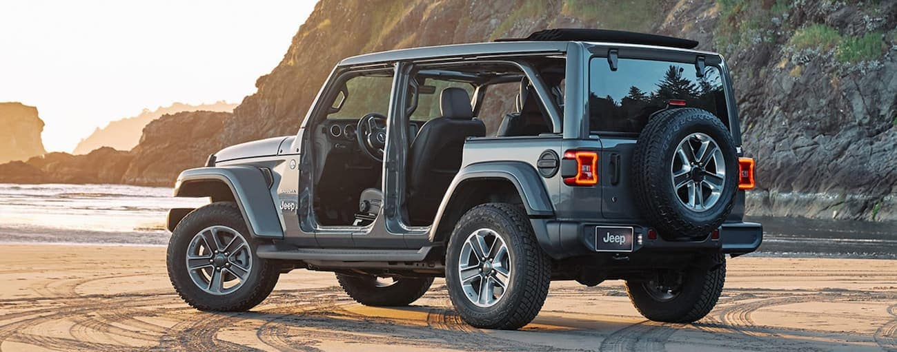 A silver 2020 Jeep Wrangler Unlimited is parked on beach sand with the doors and roof off for a comparison of the 2020 Jeep Wrangler vs 2020 Jeep Wrangler Unlimited.