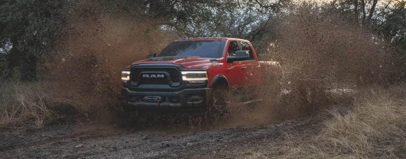 A red 2020 Ram 2500 Power Wagon is driving in a mud pit after winning the 2020 Ram 2500 vs 2020 Chevy Silverado 2500HD comparison.