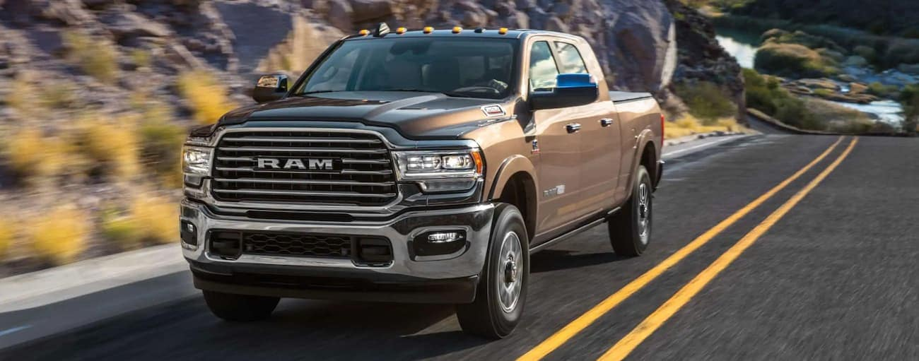 A brown 2020 Ram 2500 is driving uphill past rocky cliffs after winning the 2020 Ram 2500 vs 2020 Ford F-250 comparison.