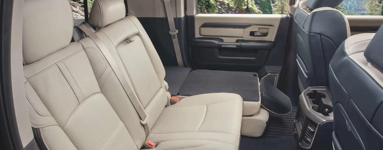 The cream interior of a 2020 Ram 2500 is shown the one of the rear seats folded down.