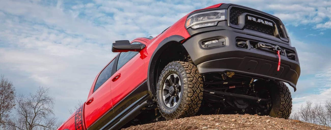 The front end of a red 2020 Ram 2500 Power Wagon is shown from a low angle while parked on a dirt mound near Costa Mesa, CA.