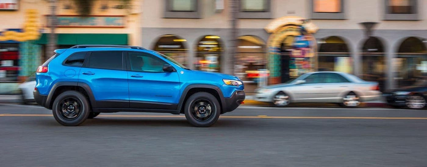 A blue 2020 Jeep Cherokee is shown from the side driving on a street in Costa Mesa, CA.