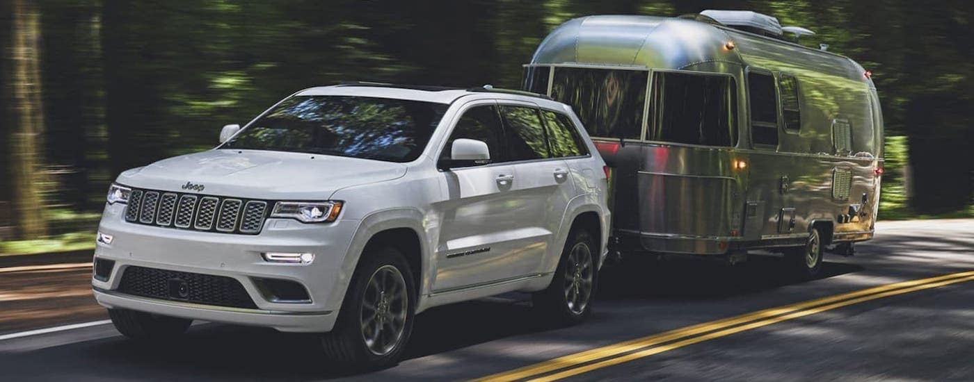 A white 2020 Jeep Grand Cherokee is towing an Airstream camper.