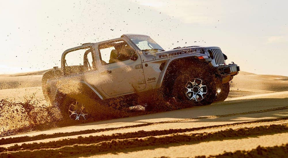 The most recognizable of the Jeep SUVs, a silver 2020 Jeep Wrangler, is kicking up sand at a beach.
