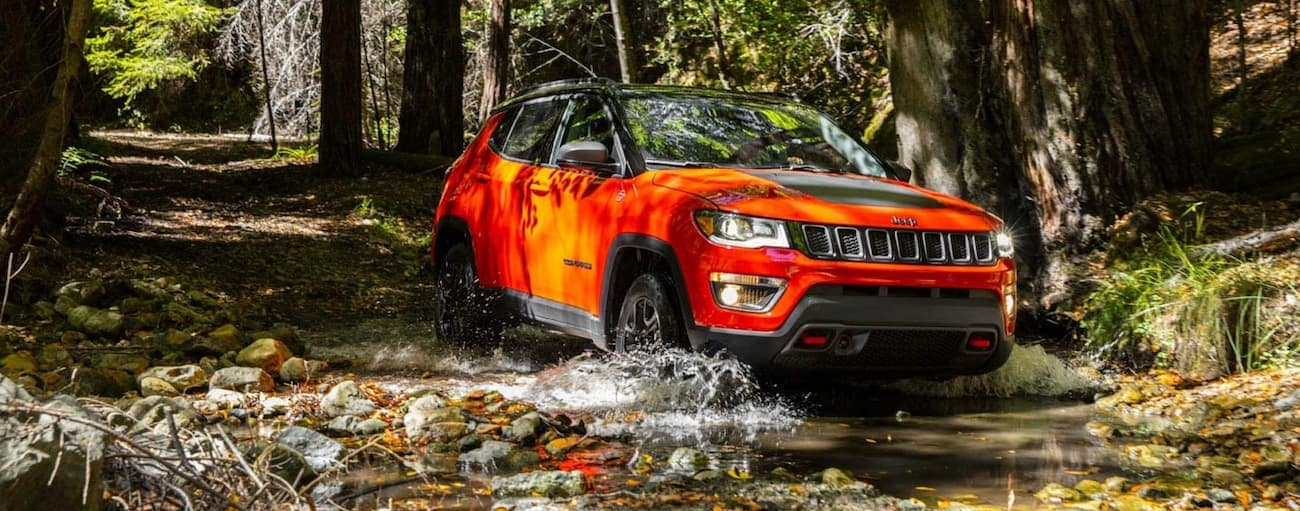 An orange 2020 Jeep Compass is off-roading through a river after winning the 2020 Jeep Compass vs 2020 Ford Escape comparison.