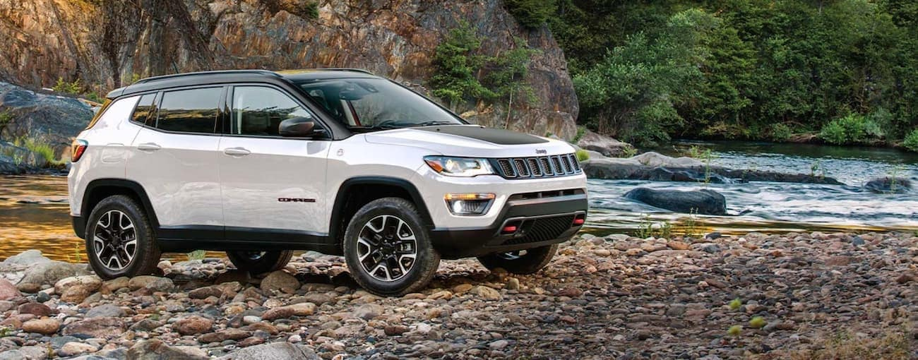 A white 2020 Jeep Compass is parked on a rocky river bed near Costa Mesa, CA.