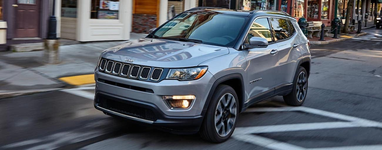 A grey 2020 Jeep Compass is driving on a city street.