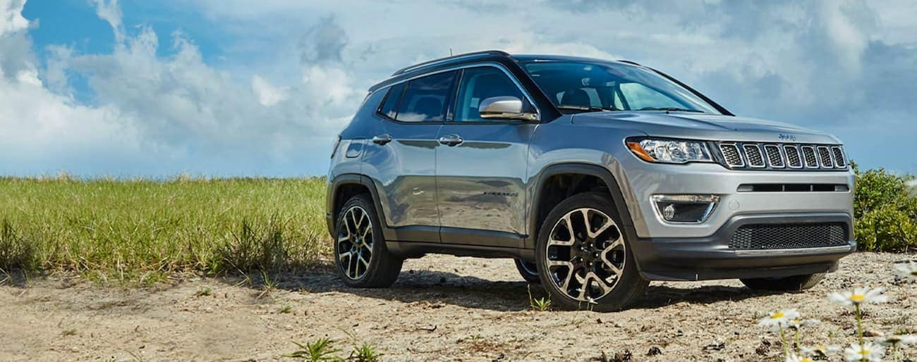 A silver 2020 Jeep Compass is parked on sand in front of grass after winning the 2020 Jeep Compass vs 2020 Nissan Rogue comparison.