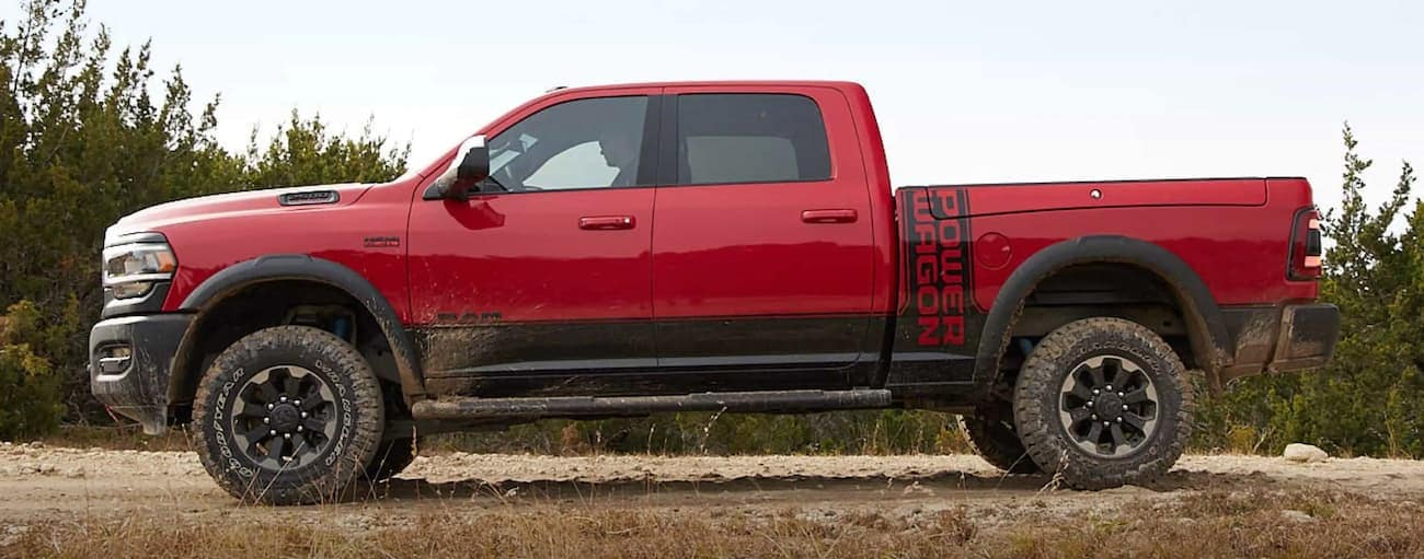 A red 2020 Ram 2500 Power Wagon is shown from the side on dirt after winning the 2020 Ram 2500 vs 2020 GMC Sierra 2500 comparison.