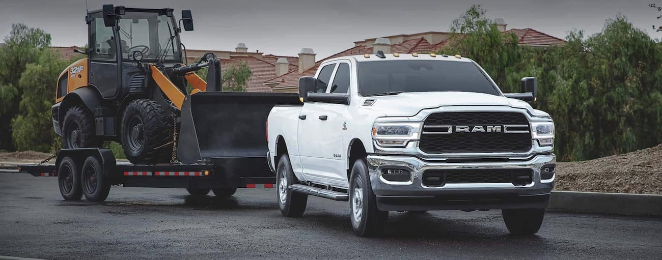 A white 2020 Ram 2500 is towing heavy equipment through a neighborhood near Costa Mesa, CA.