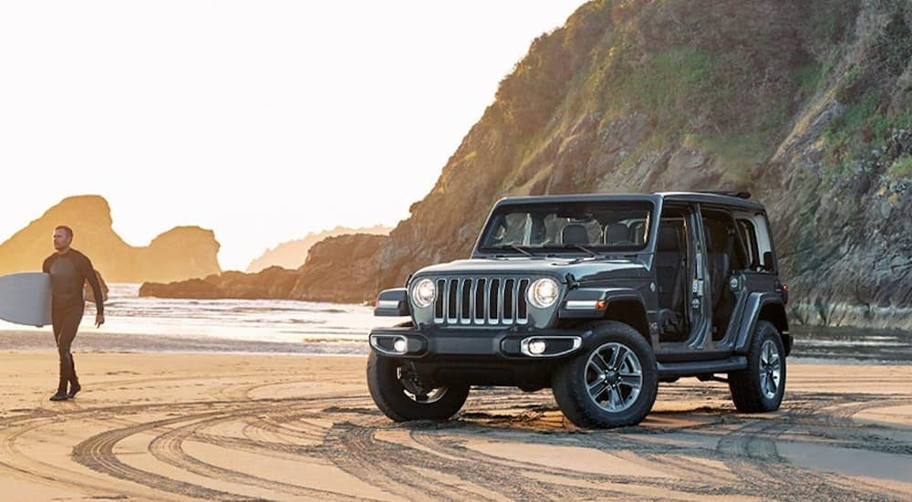 A dark grey 2018 used Jeep Wrangler Unlimited is parked on the beach near Costa Mesa, CA.