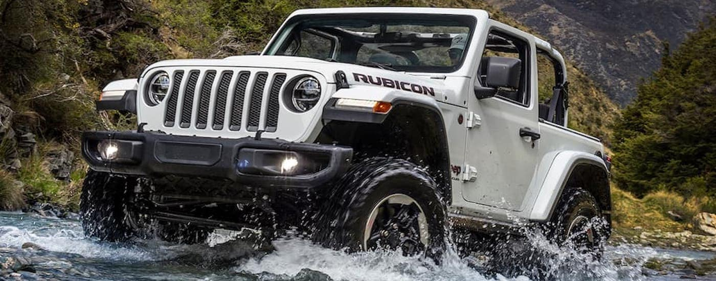 A white 2018 used Jeep Wrangler is crossing a river while off-roading.