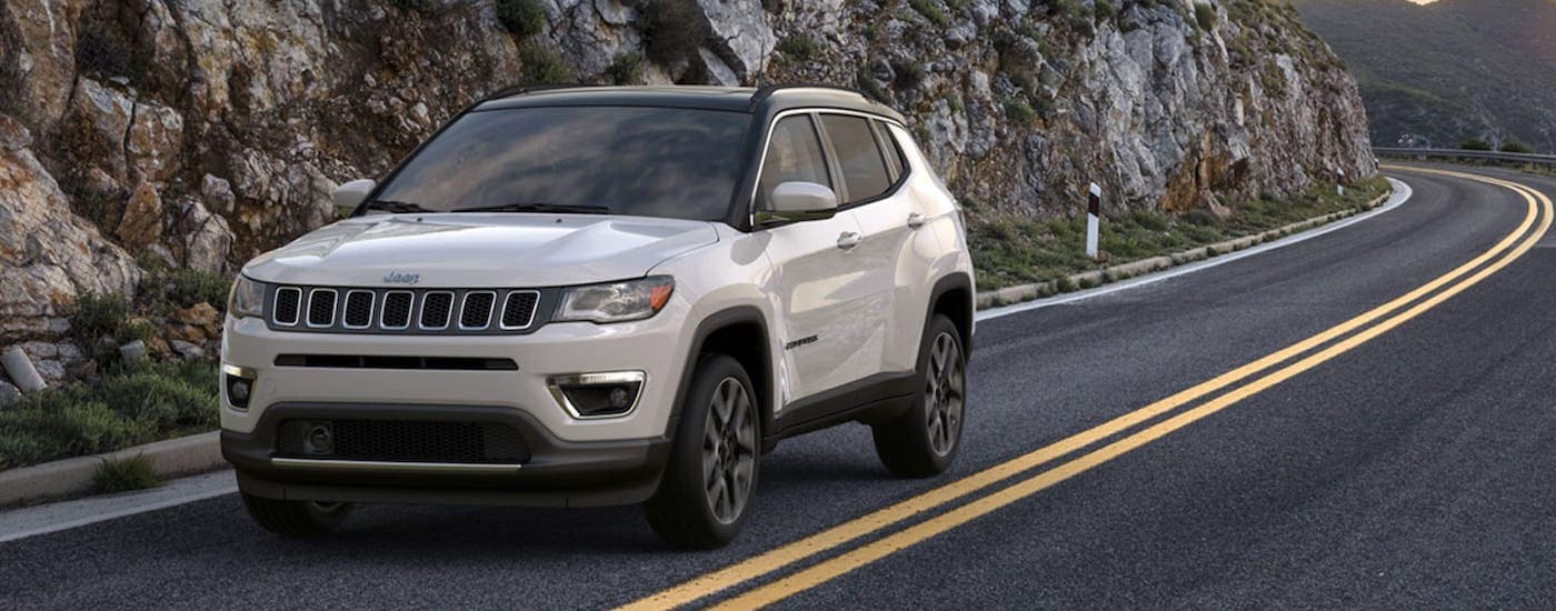 A white 2020 Jeep Compass is driving on a highway past a rock face after winning the 2020 Jeep Compass vs 2020 Honda CR-V comparison.