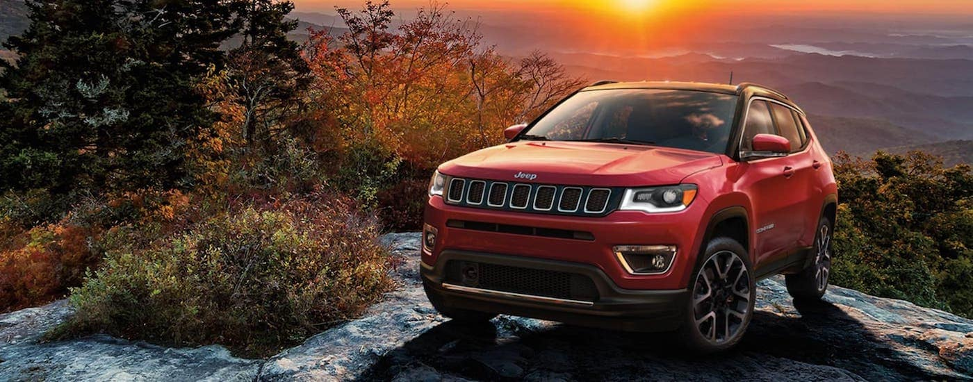 A red 2020 Jeep Compass is parked on a mountain at sunset.