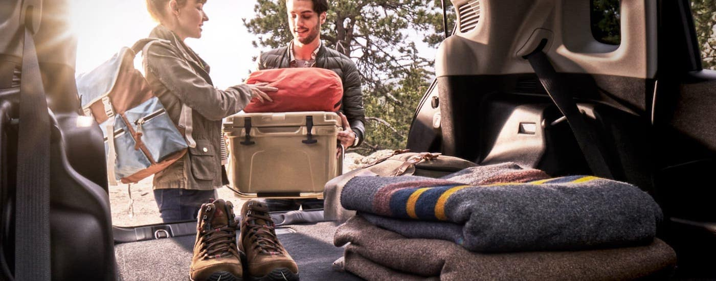 People are shown loading camping equipment into the back of a 2020 Jeep Compass.