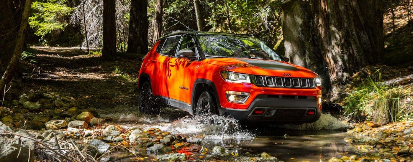 An orange 2020 Jeep Compass is driving through a river after winning the 2020 Jeep Compass vs 2020 Mazda CX-5 comparison.