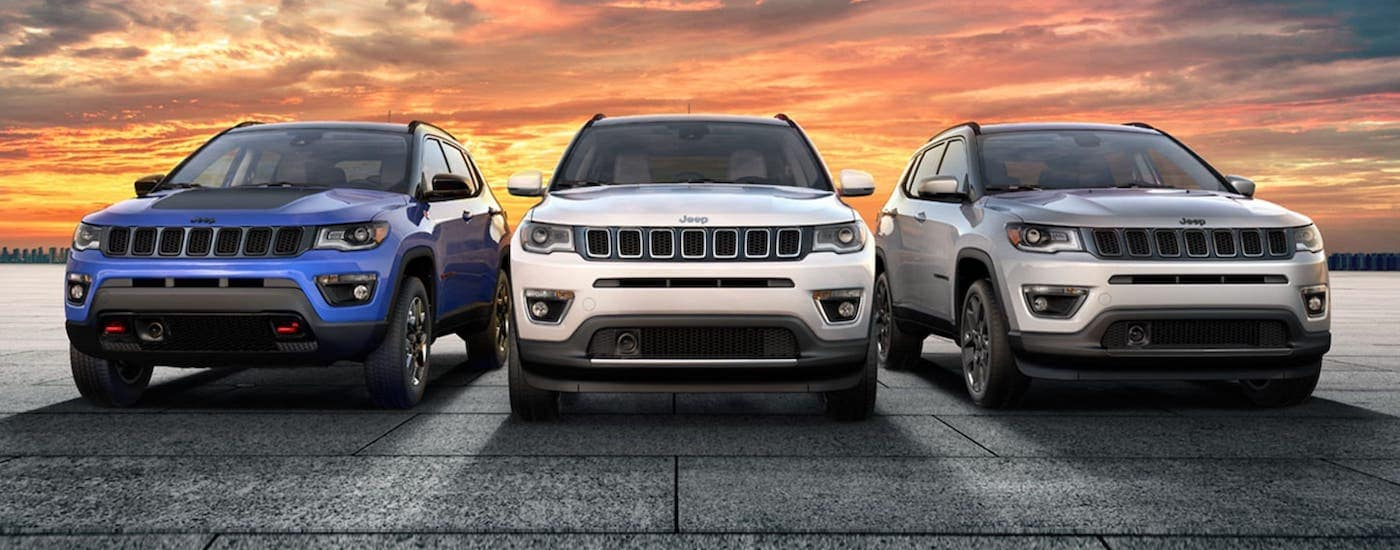 A blue, a white and a silver 2020 Jeep Compass are parked in front of a vibrant yellow and orange sunset near Costa Mesa, CA.
