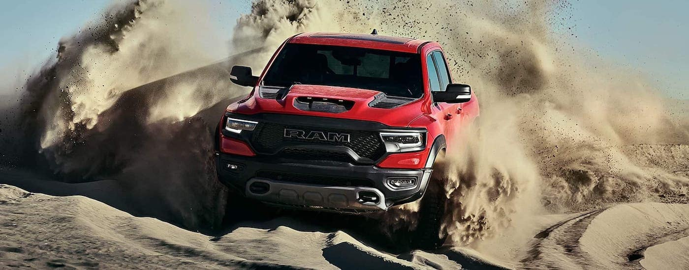 A red 2021 Ram TRX is shown from the front kicking up sand on a beach near Costa Mesa, CA.
